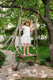 Little girl having fun on a swing outdoor. Child playing, garden playground. Royalty Free Stock Photography