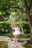Little girl having fun on a swing outdoor. Child playing, garden playground. Stock Images