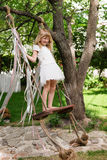 Little girl having fun on a swing outdoor. Child playing, garden playground. Royalty Free Stock Photos