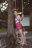 Little girl having fun on tire swing on summer day Royalty Free Stock Photo