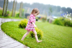 Little girl having fun under the rain Stock Photos