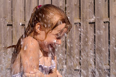Little girl having fun with water. The weather is warm but the water is cold Stock Images