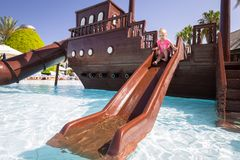 Little girl having fun at the water slide on summer holidays. Pool swimming leisure ship background sun splash vacation sunny baby blue color caucasian cute stock photography