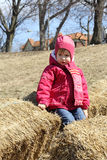 Little girl on stack of hay Royalty Free Stock Images