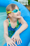 The little girl having good time in the swimming pool. The close up portrait of The little girl in the swimming glasses having good time in the swimming pool Stock Photo