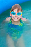 The little girl having good time in the swimming pool. The close up portrait of The little girl in the swimming glasses having good time in the swimming pool Royalty Free Stock Image