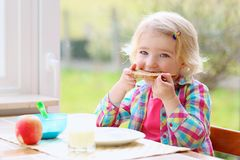 Little girl having healthy breakfast Stock Images