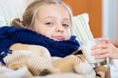 Little girl having heavy quinsy in domestic interior Stock Images