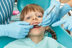 Little girl having her teeth checked by unidentified Stock Image