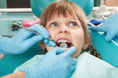 Little girl having her teeth checked by unidentified Stock Images