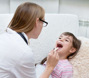 Little girl having his throat examined by health professional.  Royalty Free Stock Images