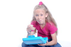 Little girl having lunch. A cute little Caucasian blond sitting girl child eating her sandwich out of her lunch box and staring. Image isolated on white studio royalty free stock photography