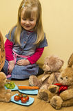 Little girl having lunch with her stuffed toys. Cute little girl in denim dress having lunch of fruits and vegetables with her stuffed animal friends stock photo