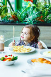 Little girl having lunch in the restaurant with the table knife and fork in hands. Royalty Free Stock Photography