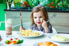 Little girl having lunch in the restaurant with the table knife and fork in hands. Stock Images
