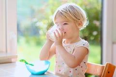 Little girl having oatmeal for breakfast royalty free stock images