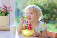 Little girl having oatmeal for breakfast Royalty Free Stock Photo