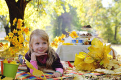 Little girl having picnic under autumn trees Royalty Free Stock Image