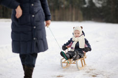 Little girl having sleight ride on winter day Stock Photo