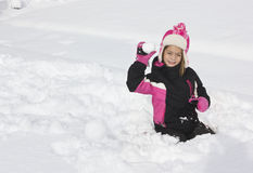Little girl having a snowball fight. On a sunny winter day a little girl gets ready start a snowball fight royalty free stock photo