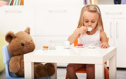 Little girl having some tea with her toy bear. Sitting at a small table sipping from a cup, shallow depth stock images