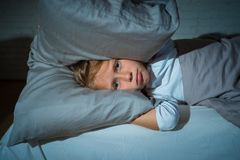 Little girl having trouble sleeping at night holding pillow covering her head and ears upset stock photos