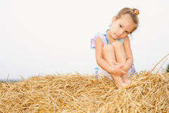 Little girl on haystack. Stock Photography