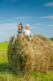 Little girl on haystack. Stock Images