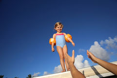 Little girl heading to the sea. Little girl in swimsuit ready to jump from pontoon Stock Images
