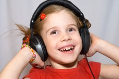 Little girl with headphones. Smiling little girl listening to music with headphones Royalty Free Stock Photos