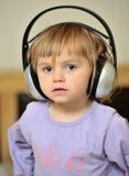 Little girl with headphones Stock Photos
