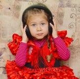 Little girl with headphones Stock Image