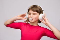 Little girl with headphones chewing gum on white stock image