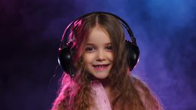 Little girl in headphones dancing on smoky background, slow motion stock video footage
