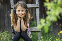 Little girl in headphones enjoying music in nature. Stock Image