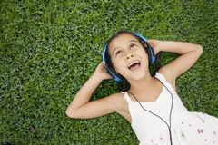 Little girl with headphones listening music Stock Images