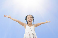 Little girl with headphones listening music Royalty Free Stock Photo