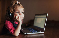 Little girl with headphones listening to music, using laptop Stock Photo