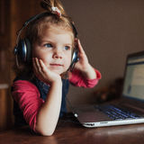 Little girl with headphones listening to music, using laptop Stock Photography