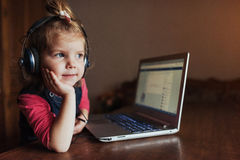 Little girl with headphones listening to music, using laptop Stock Photos