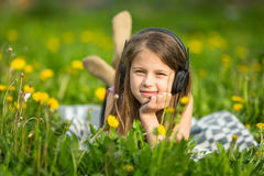 Little girl in headphones lying in the green grass. Happy. Stock Photos