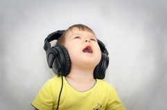 Little girl with headphones singing song Stock Photos