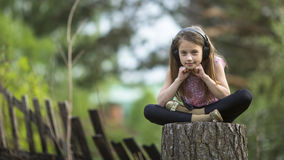 Little girl in headphones sitting thoughtfully. Outdoors Royalty Free Stock Photo