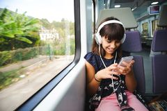 Little girl with headphones and smart phone travelling by train stock photos