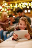 Little girl with headphones is using a tablet on Christmas day. Cute little girl with headphones is using a tablet on Christmas day stock photo