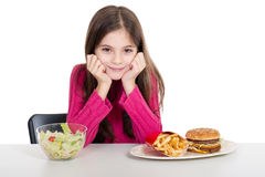 Little girl with healthy. Smiling little girl with healthy and unhealthy food Stock Image