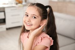 Little girl with hearing aid. At home stock photography