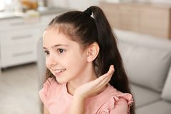 Little girl with hearing aid. At home royalty free stock photo