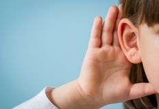 Little girl with hearing problem on light blue background. Close up, copy space. Child with hearing problem on blue background. Hearing loss in childhood stock photo