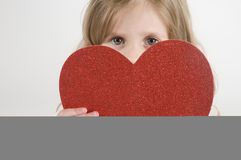 Little Girl with a Heart. Little girl holding a heart shape Royalty Free Stock Photo